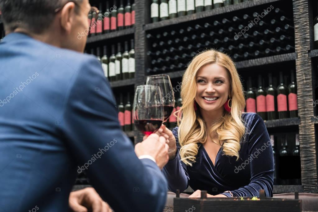 attractive adult couple clinking glasses of wine at restaurant