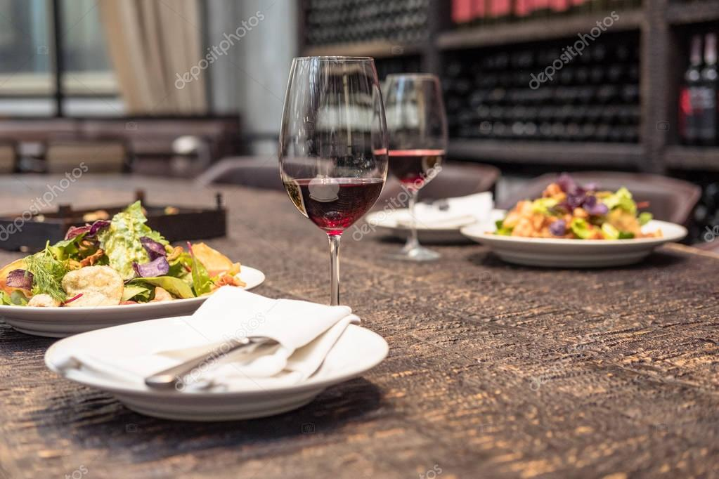 delicious salad with wine on rustic wooden table for romantic dinner at luxury restaurant