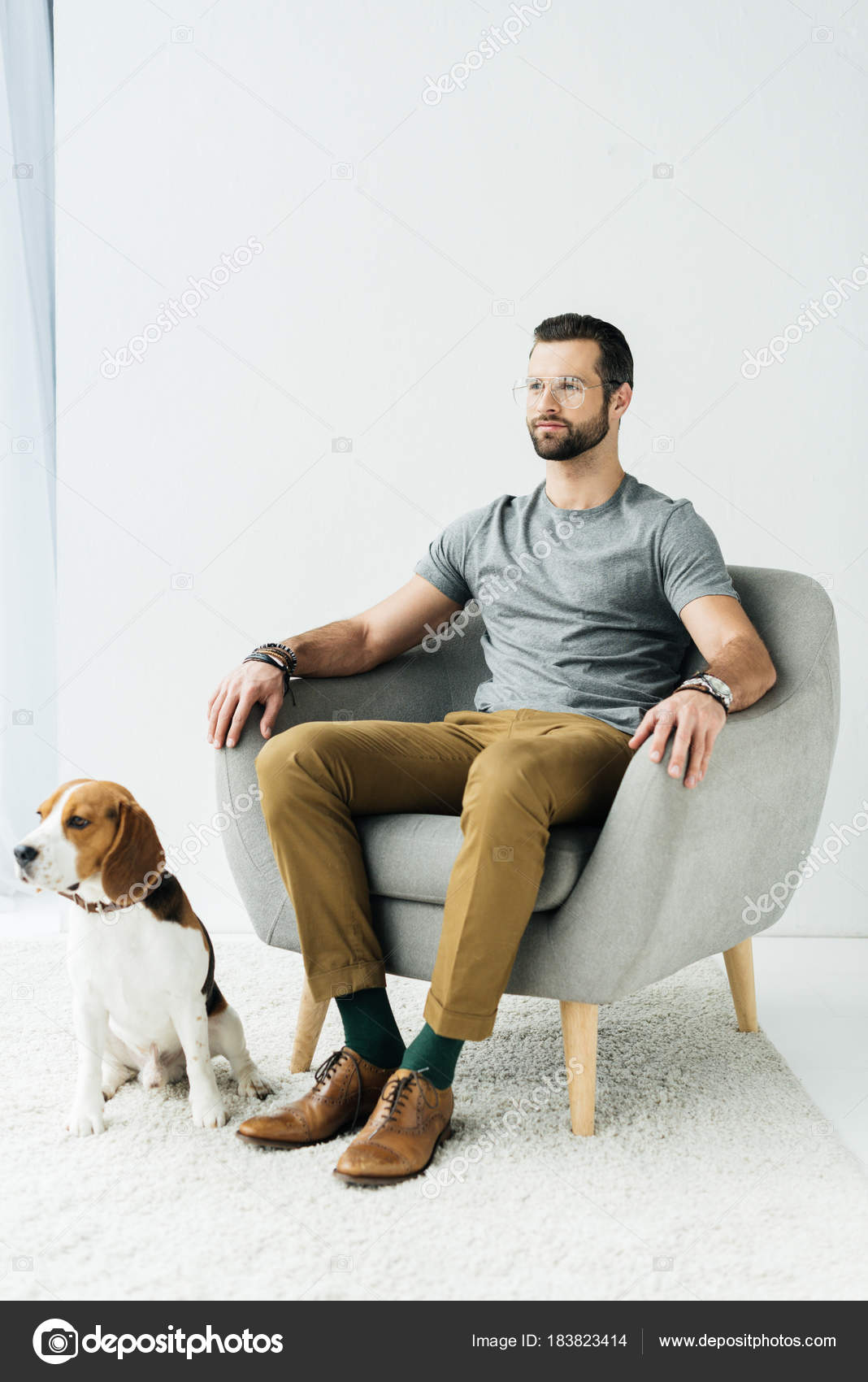 Man sitting armchair dog sitting floor stock photo y for Sitting in armchair