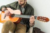 Fotografia uomo bello che gioca chitarra acustica
