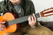 Photo cropped image of man playing barre chord on acoustic guitar