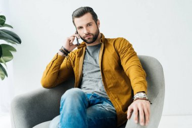 handsome man talking by smartphone and looking at camera