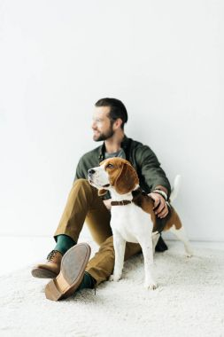 handsome man sitting with cute beagle on carpet