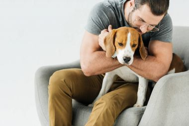 man hugging dog and sitting on armchair isolated on white