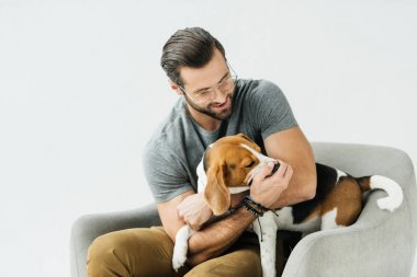 smiling handsome man playing with dog on armchair isolated on white
