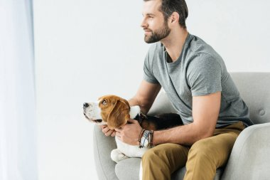 side view of handsome man sitting on armchair with dog