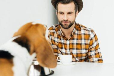 man sitting at table and looking at dog