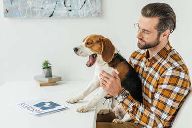 businessman holding yawning dog at table