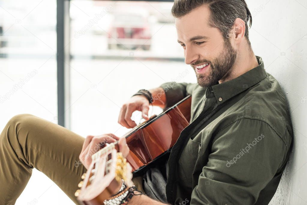 side view of handsome smiling man playing acoustic guitar
