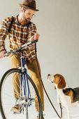 Fotografie pěkný bicycler s beagle s vodítko na bílém