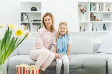 smiling daughter and mother sitting on sofa in living room