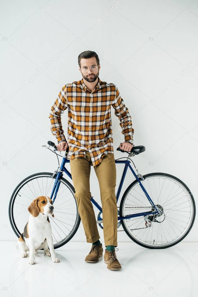 handsome bicycler standing with beagle and looking at camera on white