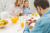 Photo selective focus of man having breakfast together with family at home