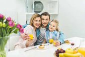 Photo portrait of smiling parents and daughter looking at camera during breakfast at home