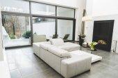 Zobrazit prázdné obývacího pokoje s bílou pohovkou a kytici květin na konferenční stolek
