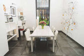Photo view of stylish empty dining room with bouquet of tulips on table