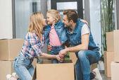 Ať se usmívám rodiče a malá dcerka v krabici v nové domácnosti, přesunutí koncept domova