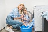 anya és lánya látszó-on fényképezőgép-mialatt ruhák mosógép otthon