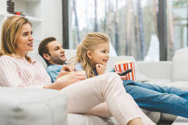 side view of family with popcorn watching film together at home
