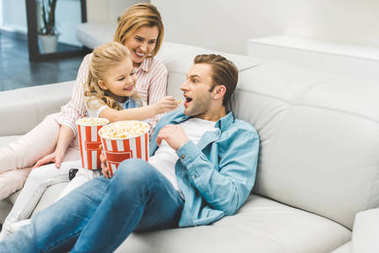 happy family with popcorn watching film together at home