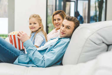 side view of family with popcorn looking at camera while watching film together at home