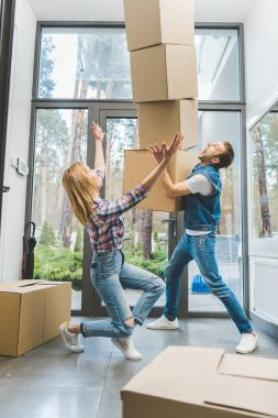 couple catching falling cardboard boxes, moving home concept