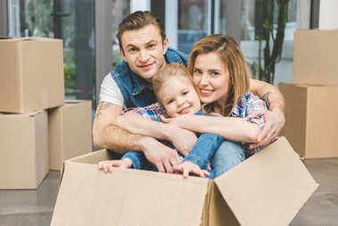 portrait of smiling parents and little daughter in cardboard box at new home, moving home concept