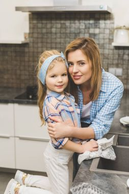portrait of mother hugging daughter while washing dishes after dinner in kitchen