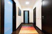 pohled z chodby s dřevěnými dveřmi v bytě