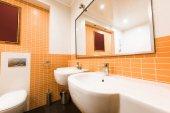 zblízka pohled na moderní koupelny v oranžové a bílé barvy