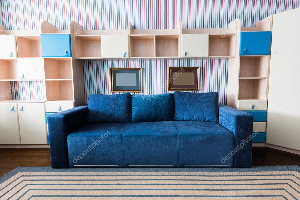 close up view of blue sofa and wooden closet in living room