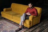 Photo fashionable elegant man sitting on yellow couch