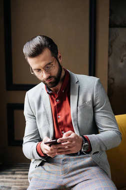 handsome stylish man in glasses using smartphone