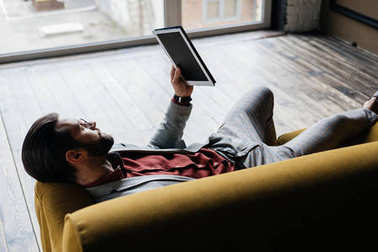 stylish handsome man using digital tablet while lying on couch