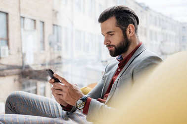 stylish handsome man using smartphone and sitting at window