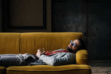 drunk man in sunglasses with glass of cognac lying on yellow sofa in loft interior