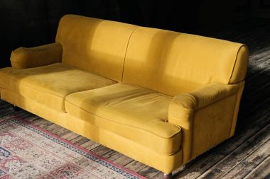 yellow couch on wooden floor with carpet