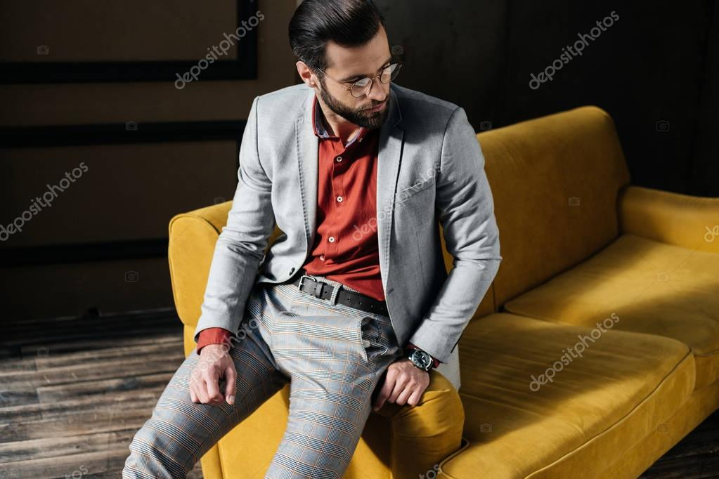 fashionable elegant man in glasses and suit sitting on couch