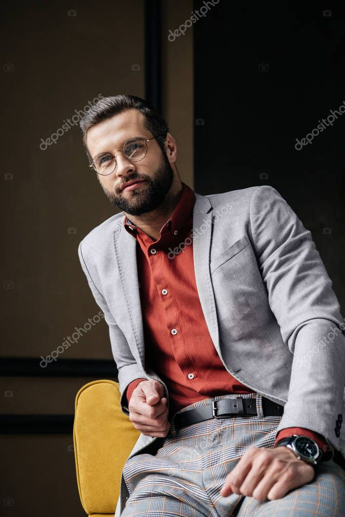 handsome stylish elegant man in glasses and suit sitting on couch