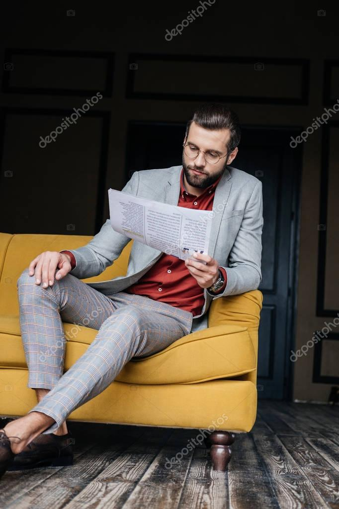 handsome man in trendy suit reading newspaper and sitting on couch