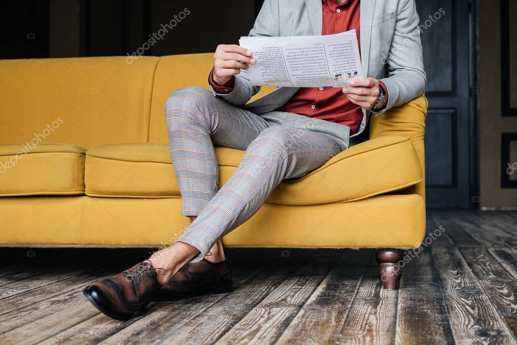 cropped view of stylish man sitting on couch with newspaper