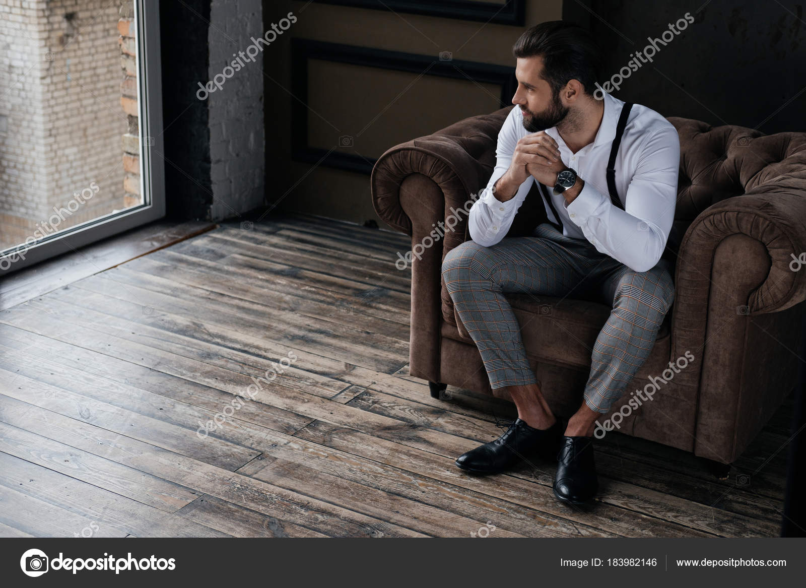 Handsome stylish man sitting armchair looking window loft for Sitting in armchair