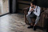 Fotografia uomo alla moda bello seduto in poltrona e guardando la finestra, soppalco interno