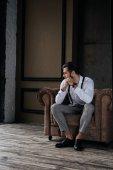 Fotografia uomo elegante pensive indoeuropeo seduto in poltrona in interiore del granaio