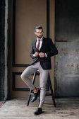 Fotografie schöne stilvolle Geschäftsmann im Anzug posiert auf Hocker im Loft Interieur