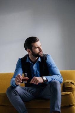 stylish man holding alcohol drink and sitting on yellow sofa