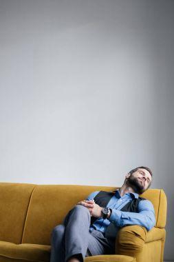 handsome stylish man resting on yellow sofa