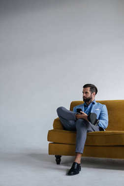 stylish man in blue trendy suit holding smartphone and sitting on yellow sofa