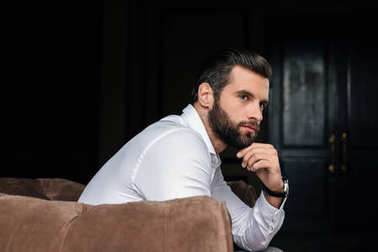 thoughtful handsome bearded man sitting in armchair