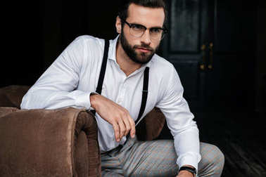 handsome elegant man in eyeglasses, white shirt and suspenders sitting in armchair